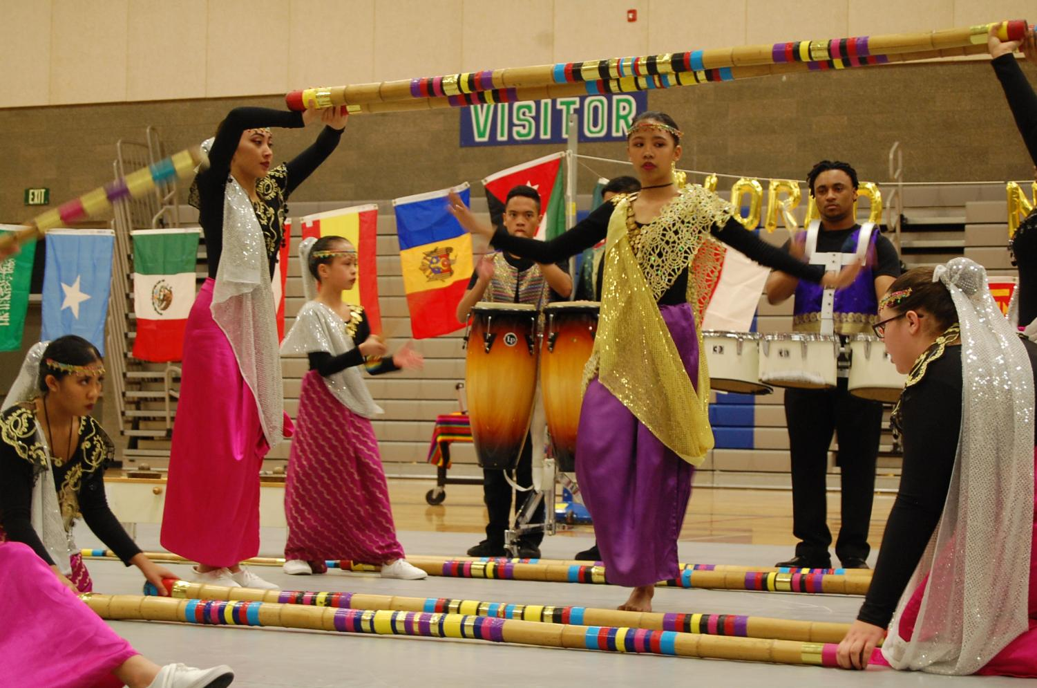 FYA+demonstrates+%E2%80%9Ctinikling%E2%80%9D+which+is+a+folk+dance+in+the+Philippines+that+involves+two+people+hitting+and+sliding+bamboo+poles+on+the+ground+while+one+or+more+other+dances+dance+over%2C+between%2C+and+on+the+poles